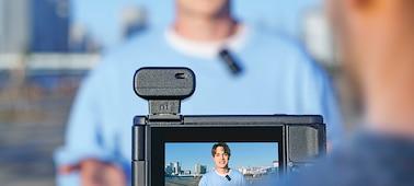 Kuva kahdesta henkilöstä, jotka tallentavat ääntään ECM-W2BT-mikrofonilla käyttäen lähetintä ja vastaanotinta