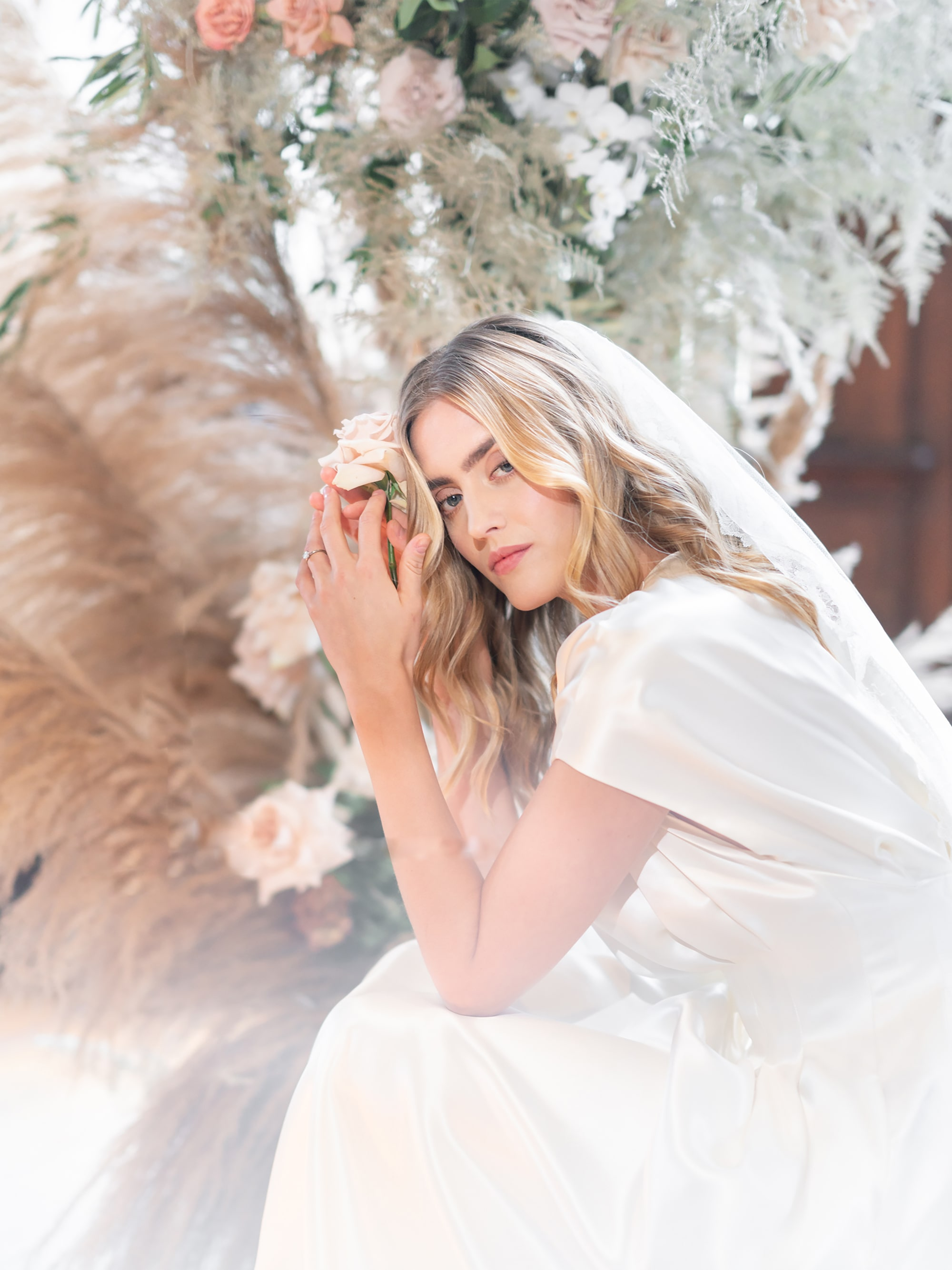 sandra-aberg-sony-alpha-7r3-bride-with-a-veil-is-sitting-in-front-of-a-feather-bouquet-with-a-rose-in-her-hands