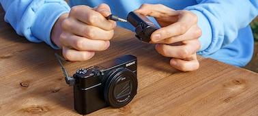 Henkilö liittää ECM-W2BT:n kaapelilla yhteensopivaan kameraan 3,5mm:n stereominiliittimen kautta